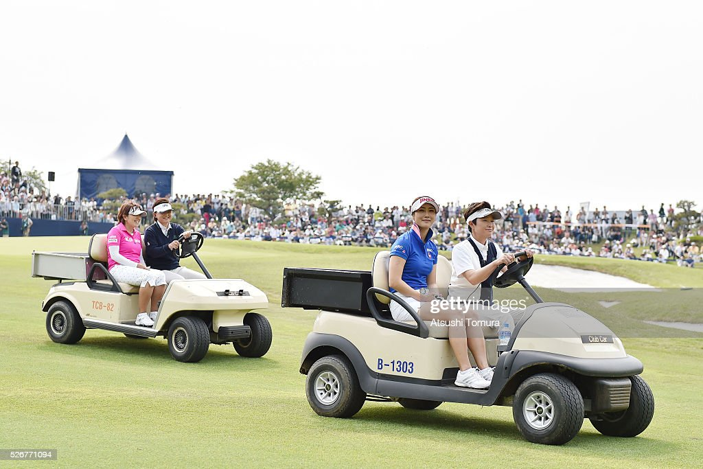 Ha-Neul Kim of South Korea (R) and Hiroko Fukushima of Japan (R) sit in golf carts as they are driven to the 18th tee for a playoff during the final round of the CyberAgent Ladies Golf Tournament at the Grand Fields Country Club on May 1, 2016 in Mishima, Japan.