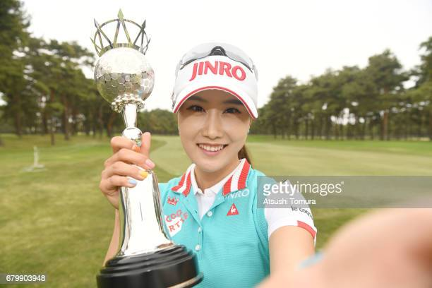 HaNeul Kim of South Korea imitates a selfie as she poses with the trophy after winning the World Ladies Championship Salonpas Cup at the Ibaraki Golf...