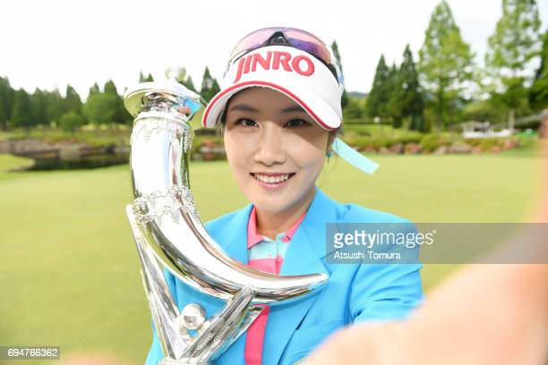 HaNeul Kim of South Korea imitates a selfie as she poses with the trophy after winning the Suntory Ladies Open at the Rokko Kokusai Golf Club on June...
