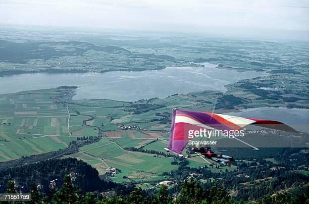 Hang glider flying over rural landscape