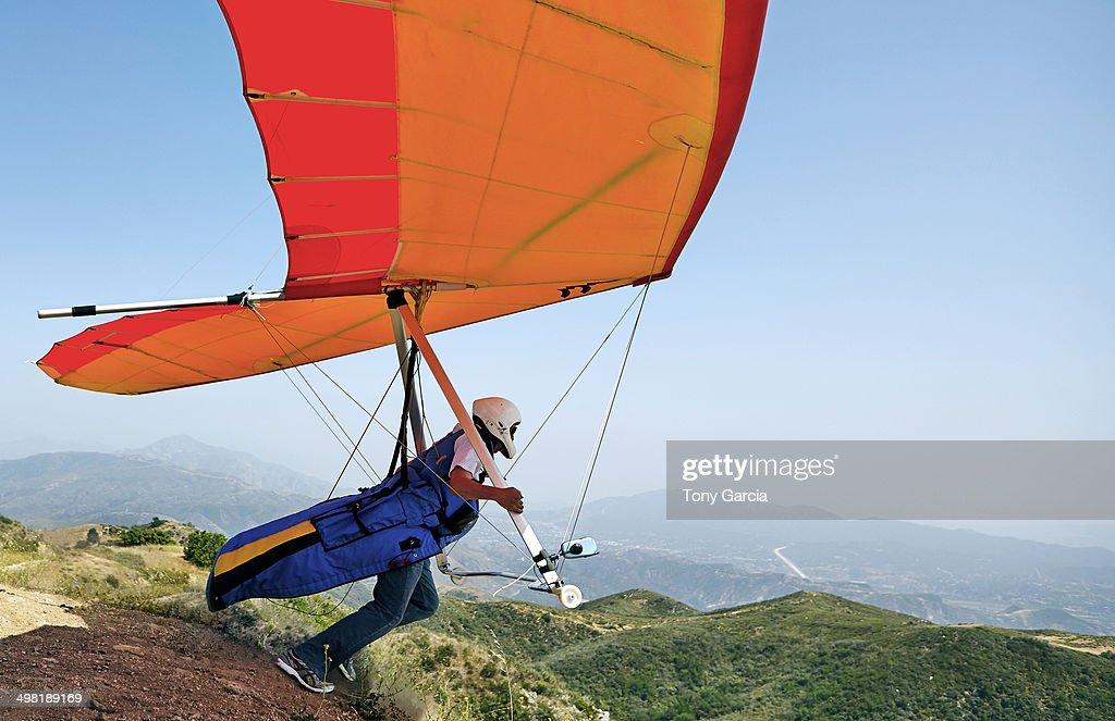 Hang glider pilot taking off