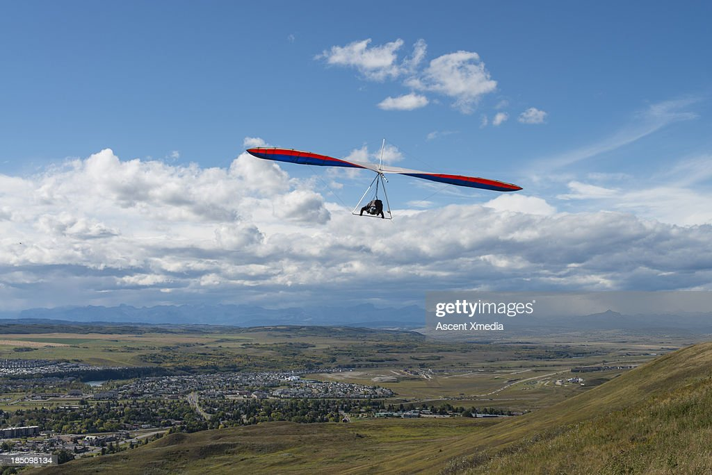 Hang glider soars above hillside, town and mtns : Stock Photo