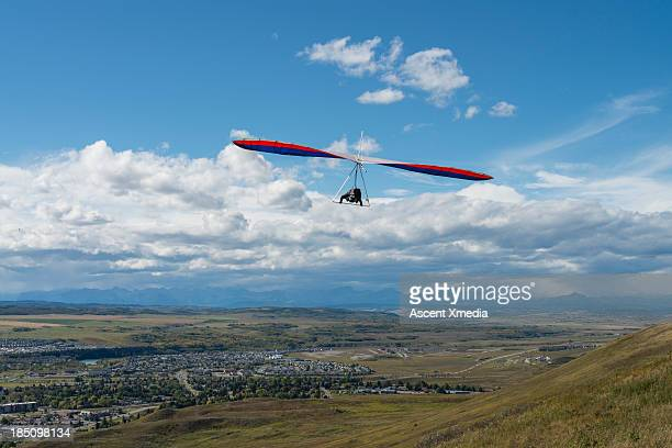 Hang glider soars above hillside, town and mtns