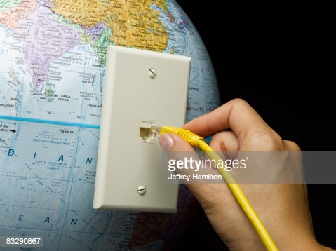 Hang plugging in ethernet cable to globe : Stock Photo