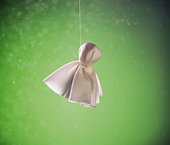 Hanged doll made of white cloth, green background