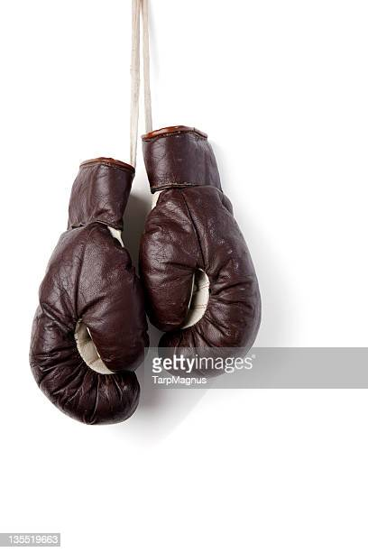 Hanging boxing gloves against white background