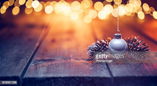 Hanging christmas ornament on old wood and defocused gold lights