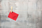 Red colored envelope is hanging on a clothesline