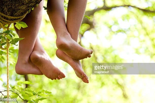 Hanging Füße von Kindern sitzen auf Baum
