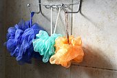 Purple, turquoise, and orange loofahs hang from a silver rack against tile in the bathroom.