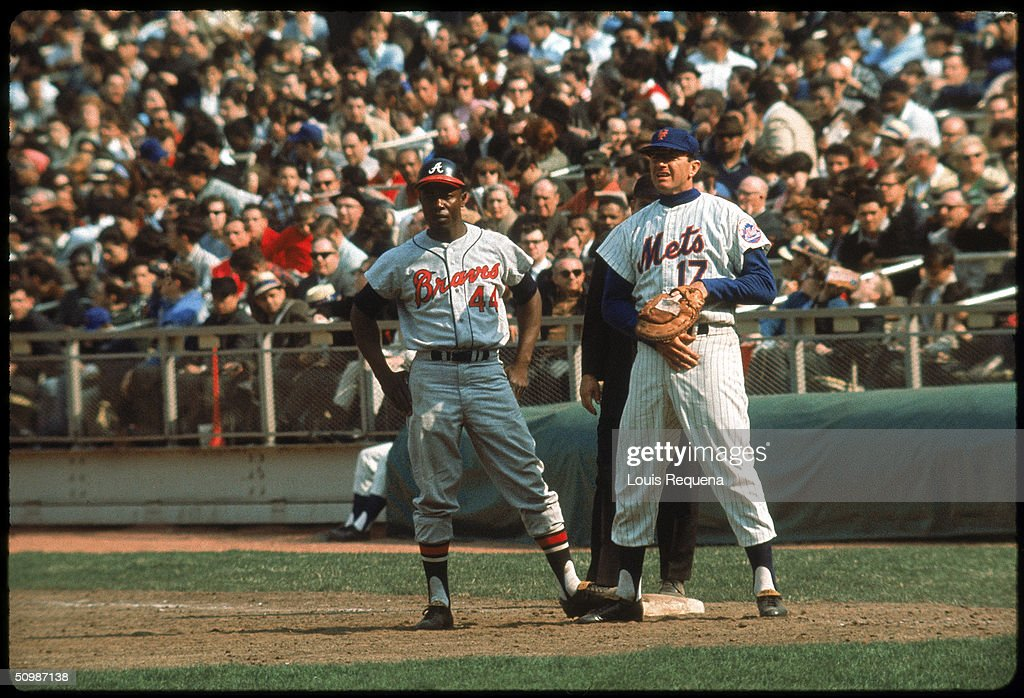 Hank Aaron of the Atlanta Braves focuses on the mound as first baseman Dick Stuart of the New York Mets holds him on during an MLB game at Shea...