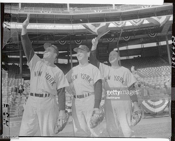 Hank Bauer Mickey Mantle and Enos Slaughter shade their eyes as they look over 'enemy' grounds at Milwaukee County Stadium where the third game of...