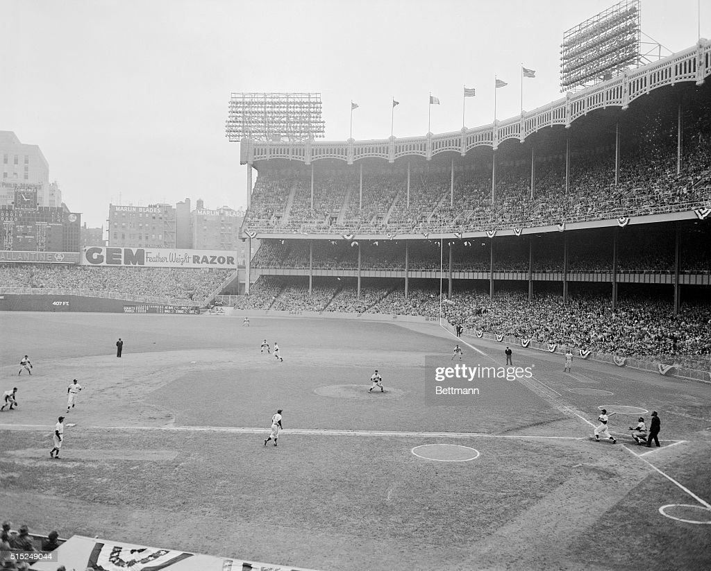 Hank Bauer triples with the bases loaded scoring Yogi Berra Joe DiMaggio and Johnny Mize during the 6th inning of the 6th World Series game at Yankee...