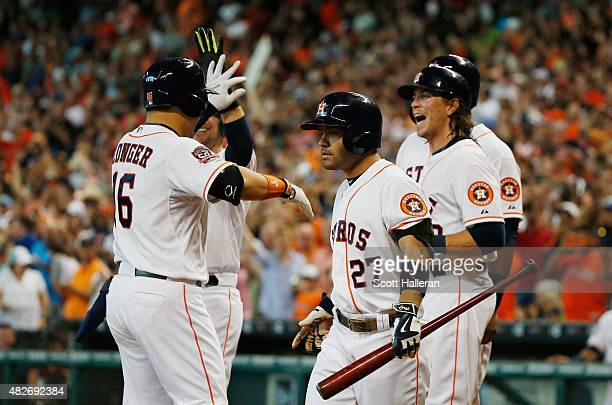 Hank Conger of the Houston Astros is greeted by his teammates after hitting a grand slam in the fourth inning off Jeremy Hellickson of the Arizona...