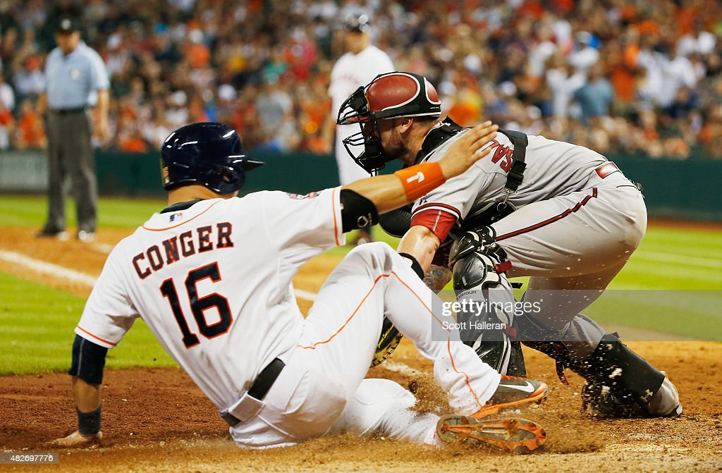 Hank Conger of the Houston Astros is tagged out at home plate by Jarrod Saltalamacchia of the Arizona Diamondbacks in the eighth inning during their...