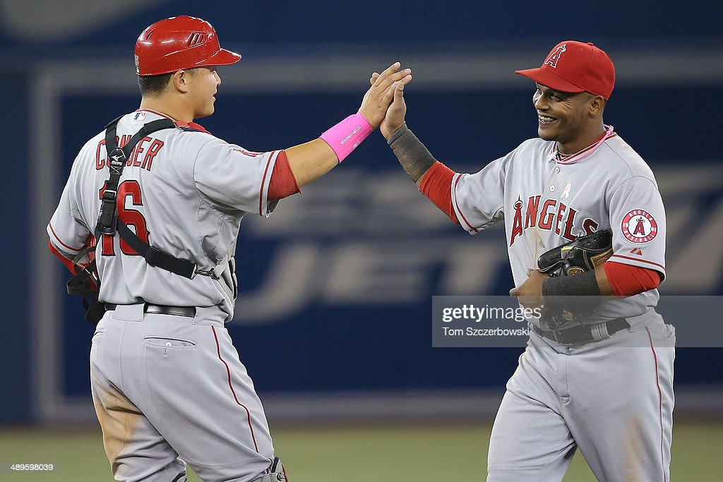 <a gi-track='captionPersonalityLinkClicked' href=/galleries/search?phrase=Hank+Conger&family=editorial&specificpeople=713039 ng-click='$event.stopPropagation()'>Hank Conger</a> #16 of the Los Angeles Angels of Anaheim celebrates their victory with <a gi-track='captionPersonalityLinkClicked' href=/galleries/search?phrase=Erick+Aybar&family=editorial&specificpeople=551376 ng-click='$event.stopPropagation()'>Erick Aybar</a> #2 during MLB game action against the Toronto Blue Jays on May 11, 2014 at Rogers Centre in Toronto, Ontario, Canada.