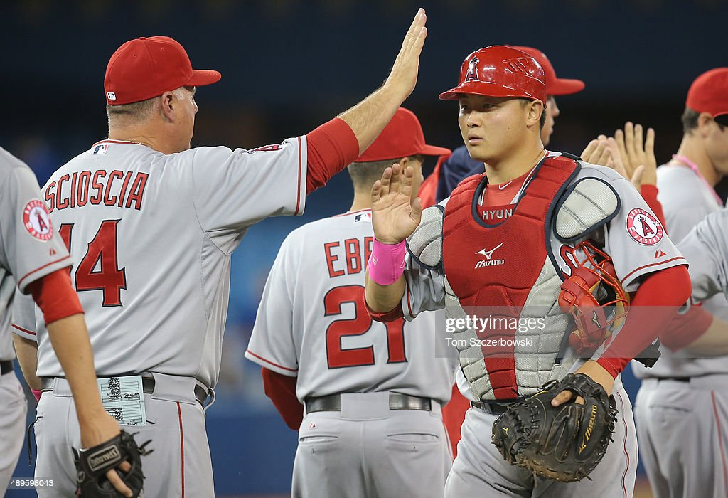 <a gi-track='captionPersonalityLinkClicked' href=/galleries/search?phrase=Hank+Conger&family=editorial&specificpeople=713039 ng-click='$event.stopPropagation()'>Hank Conger</a> #16 of the Los Angeles Angels of Anaheim is congratulated on their victory by manager <a gi-track='captionPersonalityLinkClicked' href=/galleries/search?phrase=Mike+Scioscia&family=editorial&specificpeople=206319 ng-click='$event.stopPropagation()'>Mike Scioscia</a> #14 during MLB game action against the Toronto Blue Jays on May 11, 2014 at Rogers Centre in Toronto, Ontario, Canada.