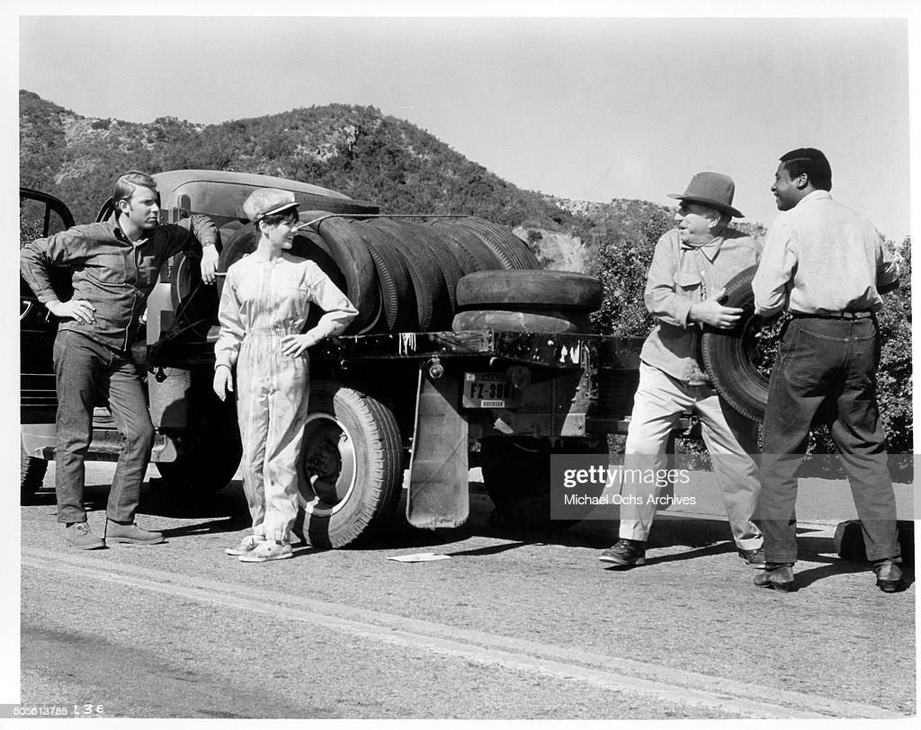 Hank Williams Jr Ed Begley and D'Urville Martin borrow a tire from Shelley Fabares in a scene from the movie 'A Time to Sing' circa 1968