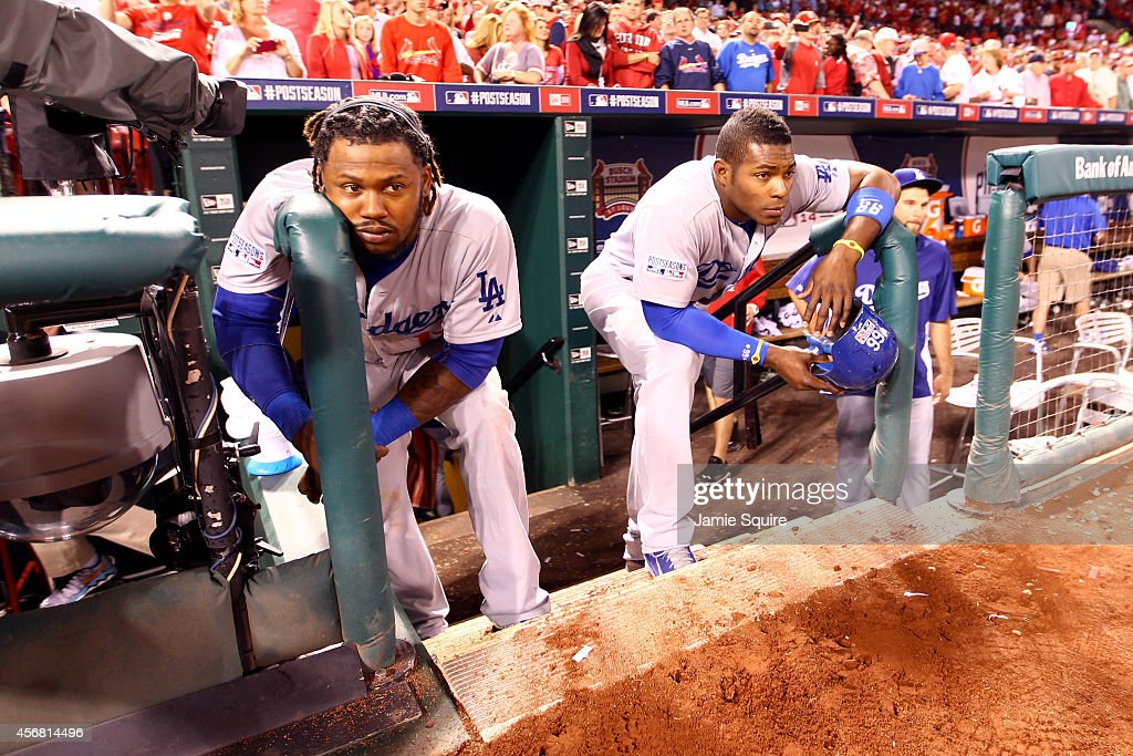 Hanley Ramirez #13 and Yasiel Puig #66 of the Los Angeles Dodgers look on from the dugout steps after being defeated by the St. Louis Cardinals in Game Four of the National League Divison Series at Busch Stadium on October 7, 2014 in St Louis, Missouri.