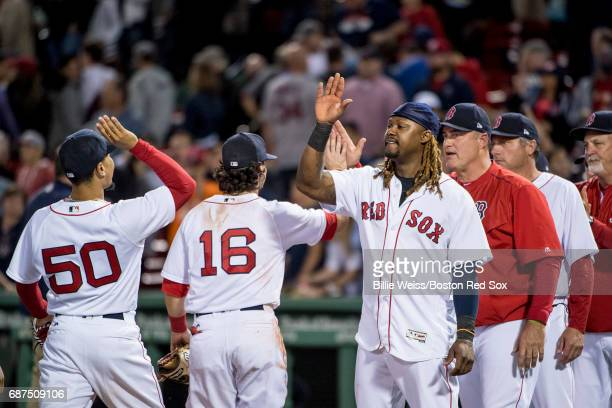 Hanley Ramirez of the Boston Red Sox high fives Andrew Benintendi and Mookie Betts after a game against the Texas Rangers on May 23 2017 at Fenway...