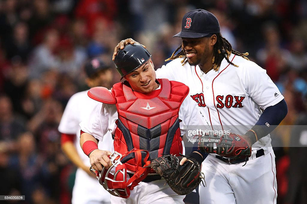 Hanley Ramirez #13 of the Boston Red Sox reacts with Christian Vazquez #7 during the second inning of a game against the Colorado Rockies on May 24, 2016 at Fenway Park in Boston, Massachusetts.