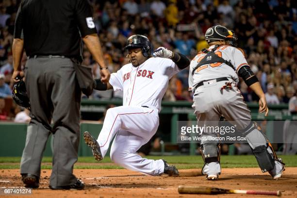Hanley Ramirez of the Boston Red Sox slides as he scores during the second inning of a game against the Baltimore Orioles on April 11 2017 at Fenway...
