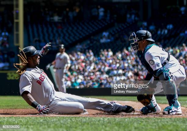 Hanley Ramirez of the Boston Red Sox slides home safely against Carlos Ruiz of the Seattle Mariners in the second inning to score on a sacrifice fly...