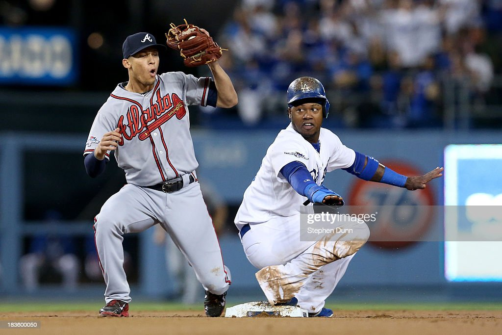 Hanley Ramirez of the Los Angeles Dodgers and Andrelton Simmons of the Atlanta Braves react after Ramirez steals second base in the first inning in...