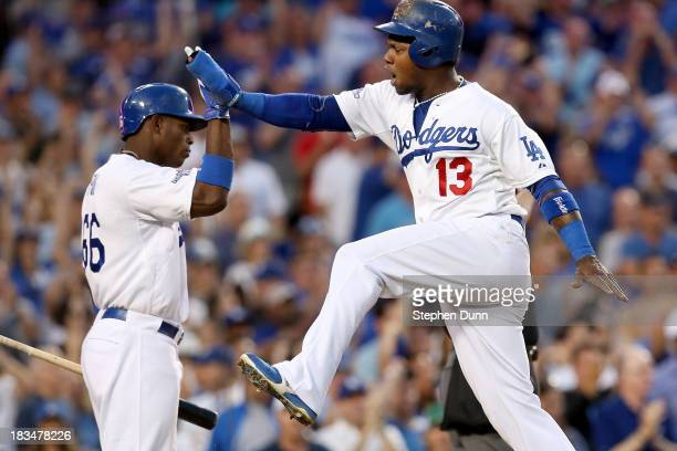 Hanley Ramirez of the Los Angeles Dodgers celebrates with Yasiel Puig as Ramirez scores a run in the third inning against the Atlanta Braves during...