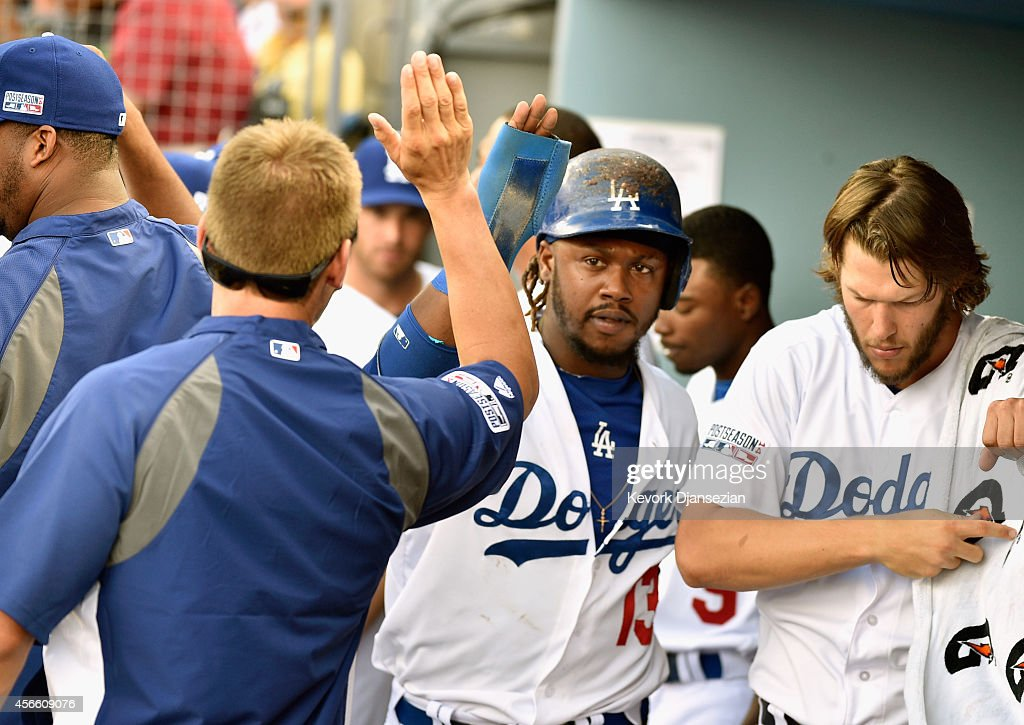 Hanley Ramirez of the Los Angeles Dodgers is congratulated by teammates after scoring on a double by Matt Kemp in the third inning during Game One of...