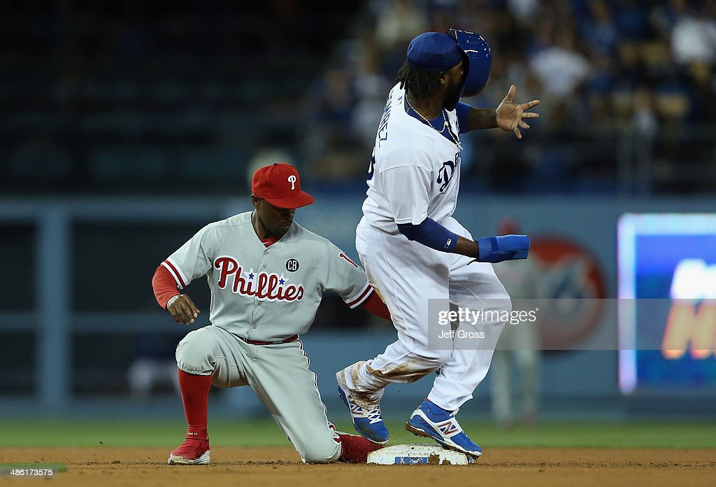 <a gi-track='captionPersonalityLinkClicked' href=/galleries/search?phrase=Hanley+Ramirez&family=editorial&specificpeople=538406 ng-click='$event.stopPropagation()'>Hanley Ramirez</a> #13 of the Los Angeles Dodgers loses his helmet as he slides safely into second past <a gi-track='captionPersonalityLinkClicked' href=/galleries/search?phrase=Jimmy+Rollins&family=editorial&specificpeople=204478 ng-click='$event.stopPropagation()'>Jimmy Rollins</a> #11 of the Philadelphia Phillies, and steals second base in the third inning at Dodger Stadium on April 22, 2014 in Los Angeles, California.
