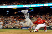 Hanley Ramirez of the Los Angeles Dodgers scores a run on a sacrifice fly hit by Andre Ethier in the tenth inning of a game against the Washington...