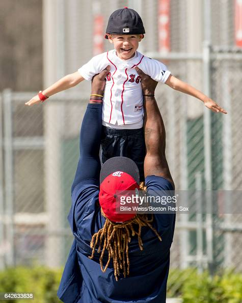 Hanley Ramirez picks up the son of Dustin Pedroia of the Boston Red Sox during a team workout on February 18 2017 at Fenway South in Fort Myers...