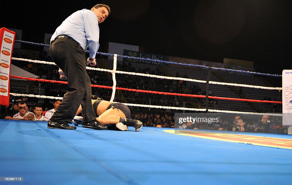 Hanna Gabriel of Costa Rica lies on the ring floor after being knocked down by Oxandia Castillo of the Dominican Republic during their World Boxing Organization super welterweight bout in San Jose on February 28, 2013. Oxandia won after round two by tecnical knockout. AFP PHOTO / Ezequiel BECERRA