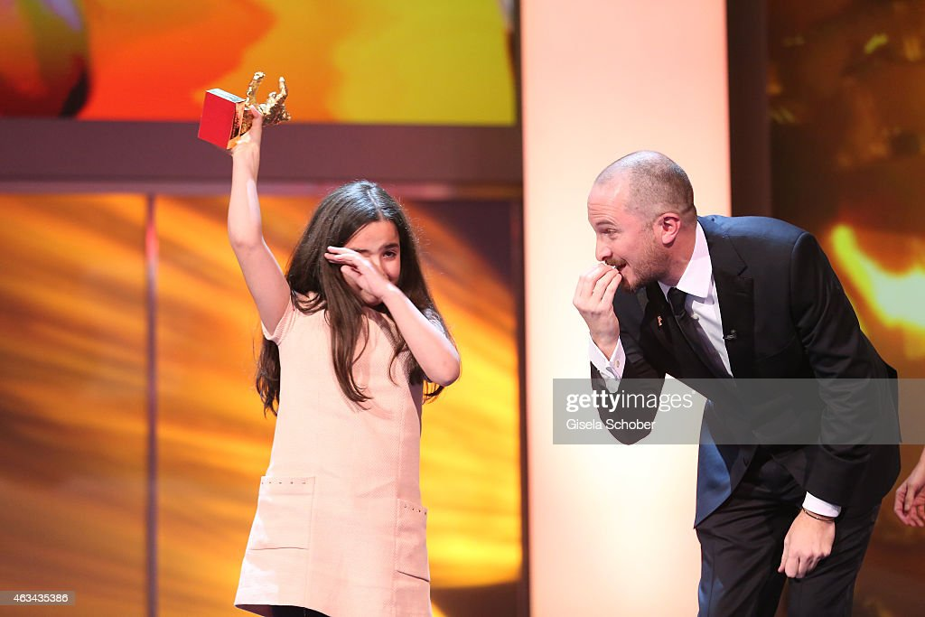 Hanna Saedi accepts the golden bear for 'Taxi' on behalf of her uncle <a gi-track='captionPersonalityLinkClicked' href=/galleries/search?phrase=Jafar+Panahi&family=editorial&specificpeople=621874 ng-click='$event.stopPropagation()'>Jafar Panahi</a> with Jury president <a gi-track='captionPersonalityLinkClicked' href=/galleries/search?phrase=Darren+Aronofsky&family=editorial&specificpeople=841696 ng-click='$event.stopPropagation()'>Darren Aronofsky</a> during the Closing Ceremony of the 65th Berlinale International Film Festival at Berlinale Palace on February 14, 2015 in Berlin, Germany.