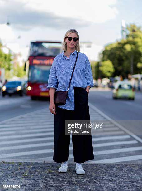 Hannah Baker wearing a blue button shirt with short sleeves and black wide pants and white sneakers and sunglasses outside Revolver Fair during the...