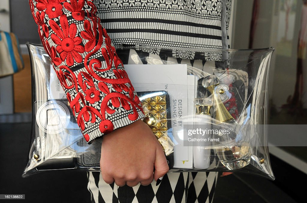 Hannah CrossKey, a student, wears a two tone ASOS suit, the jacket embellished with red applique floral motifs on the sleeves, accessorised with a see through clutch by Klear Klutch at London Fashion Week Fall/Winter 2013/14 on February 18, 2013 in London, England.
