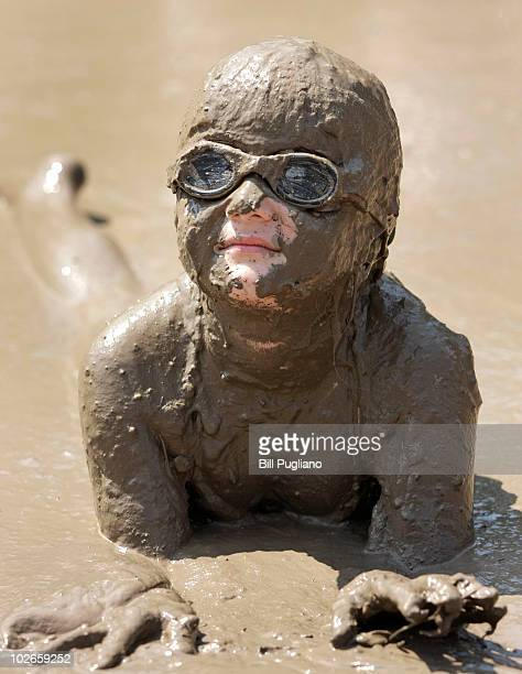 Hannah Rose Akerley age 7 of Grosse Point Park Michigan gets some relief from the heat by playing in a gigantic lake of mud at the annual Mud Day...