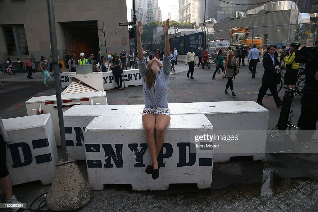 Hannah Townsend, 25, gives a prayer next to the One World Trade tower at Ground Zero on September 11, 2013 in New York City. The nation is commemorating the anniversary of the 2001 attacks which resulted in the deaths of nearly 3,000 people after two hijacked planes crashed into the World Trade Center, one into the Pentagon in Arlington, Virginia and one crash landed in Shanksville, Pennsylvania. Following the attacks in New York, the former location of the Twin Towers has been turned into the National September 11 Memorial & Museum.