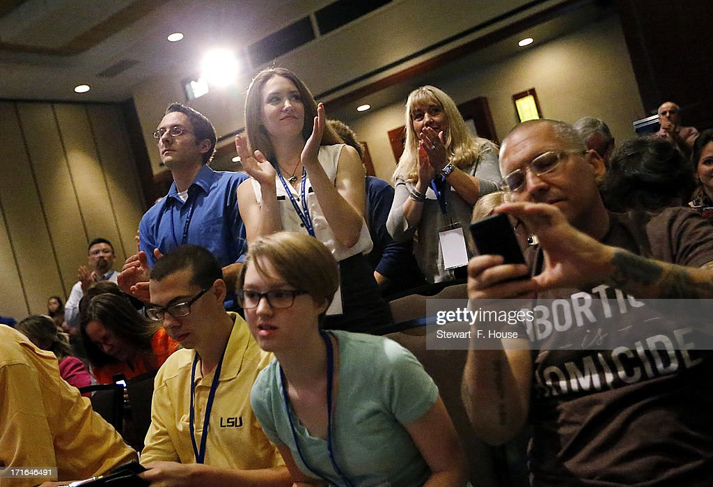Hannah Trice (C) stands to applaud during remarks by Texas Governor <a gi-track='captionPersonalityLinkClicked' href=/galleries/search?phrase=Rick+Perry+-+Politician&family=editorial&specificpeople=175872 ng-click='$event.stopPropagation()'>Rick Perry</a> during the National Right to Life Committee's opening general session at the Hyatt Regency DFW International Airport Hotel June 27, 2013 in Grapevine, Texas. Perry has reportedly vowed to continue the fight for a more restrictive abortion law in Texas after the state legislature failed to get the law passed during a special session because of a filibuster and protests.