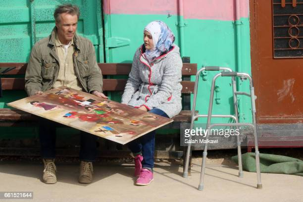 Hannes Jaenicke and Ola alKud are seen on set at the Zaatari refugee camp during the shooting of a new documentary series by German TV channel...