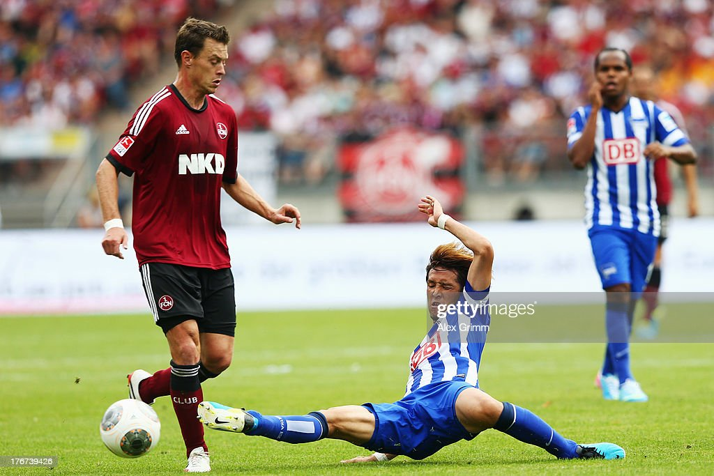 Hanno Balitsch (L) of Nuernberg is challenged by Hajime Hosogai of Berlin during the Bundesliga match between 1. FC Nuernberg and Hertha BSC Berlin at Grundig Stadium on August 18, 2013 in Nuremberg, Germany.