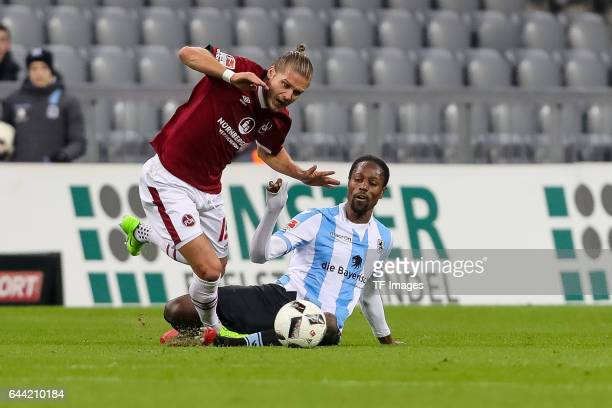 Hanno Behrens of 1 FC Nuernberg and Romuald Lacazette of TSV 1860 Muenchen battle for the ball during the Second Bundesliga match between TSV 1860...