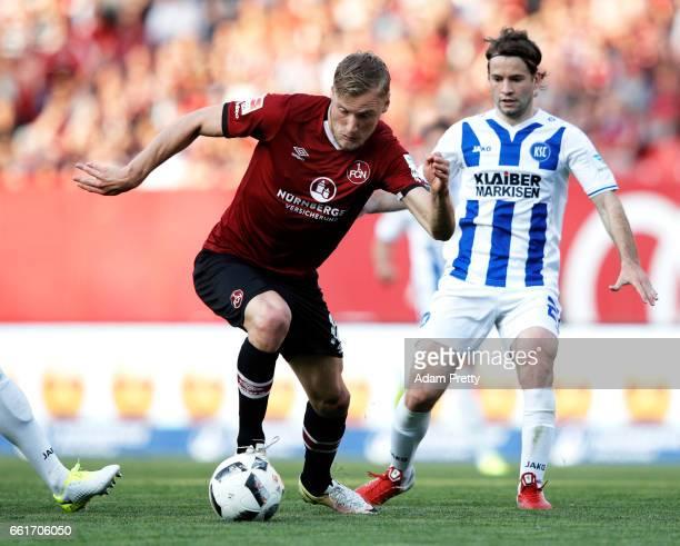 Hanno Behrens of 1FC Nuernberg is challenged by Gaeten Krebs of Karlsruher SC during the Second Bundesliga match between 1 FC Nuernberg and...