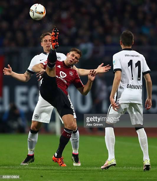 Hanno Behrens of Nuernberg is challenged by Bastian Oczipka and Mijat Gacinovic of Frankfurt during the Bundesliga Playoff Leg 2 between 1 FC...