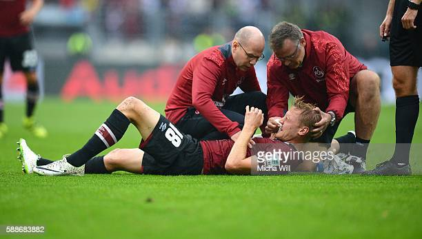 Hanno Behrens of Nuernberg is tended to as he lies with an injured nose during the Second Bundesliga match between 1 FC Nuernberg and 1 FC Heidenheim...