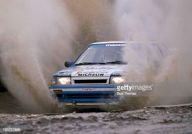 Hannu Mikkola and Christian Geistdorfer of Finland driving a Mazda 323 through a water splash during the Lombard RAC Rally circa November 1988