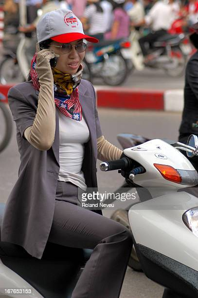 Hanoi city views and life Scooter are a fovorite transport mode in Hanoi and usually favored by women like a fashion statement A woman chatting on...
