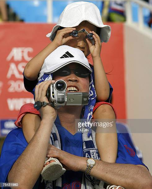 A Japanese girl watches with a telescope as she is carried on his father's shoulders during the Asian Football Cup group B match between Japan and...
