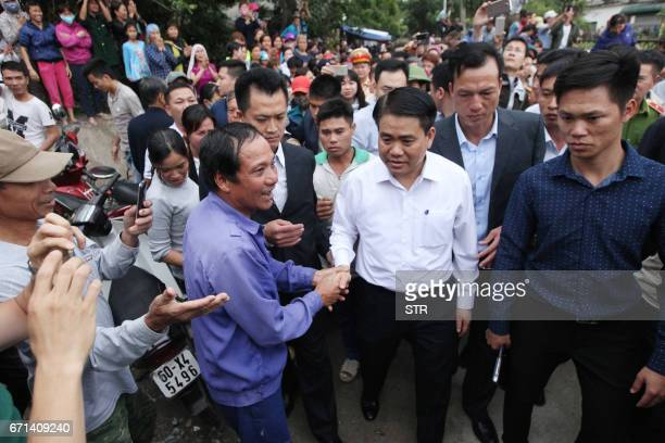 Hanoi's Mayor Nguyen Duc Chung is greeted by villagers at Dong Tam commune My Duc district in Hanoi on April 22 2017 More than a dozen police and...